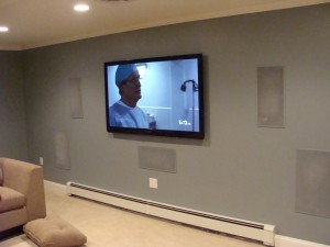 The media room screen wall with speaker grills painted and the TV installed.  Having equipment installed in the storage room eliminates the need for furniture to house the AV equipment.