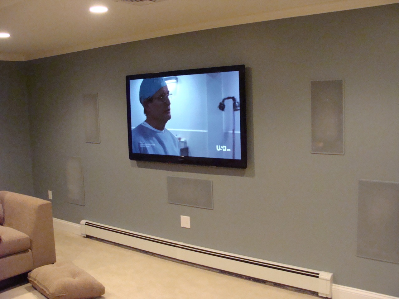 the media room screen wall with speaker grills painted and the tv installed having equipment